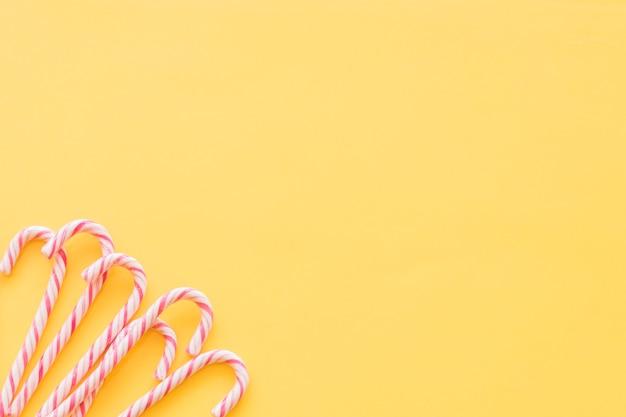 黄色の背景の隅にミント伝統的なクリスマスのキャンデー 無料写真