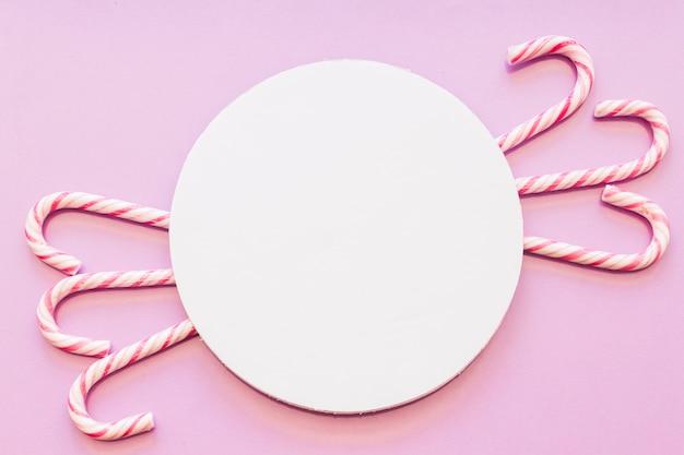 ピンクの背景にクリスマスキャンディーデザインの円形の白い空のフレーム 無料写真