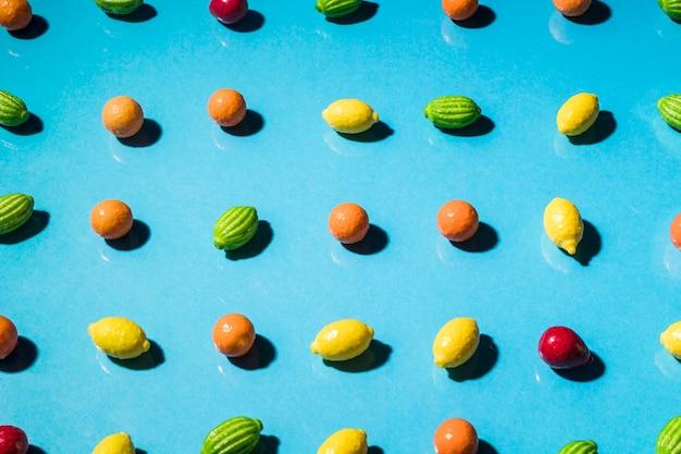 青色の背景に形作られたグミフルーツの行 無料写真