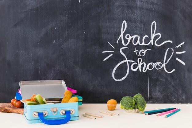 黒板の近くの鉛筆と弁当箱 無料写真