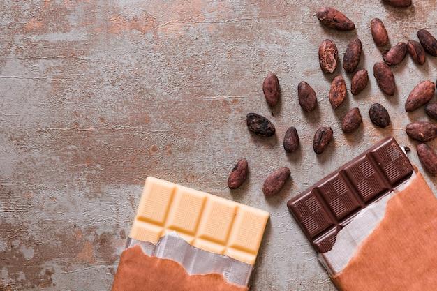 Белый и темный шоколад с сырыми какао-бобами на деревенском фоне Бесплатные Фотографии