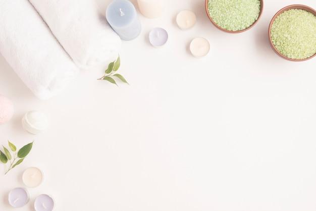 白い背景に巻き込まれたタオル、ろうそくとスパの爆弾と緑のスパの塩のボウル 無料写真