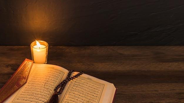 Бусы на религиозной книжке возле свечи Бесплатные Фотографии