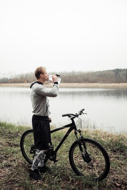Цикличная питьевая вода из бутылки, стоящая у озера Бесплатные Фотографии