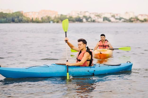 彼の友人と湖でカヤックをする男 無料写真
