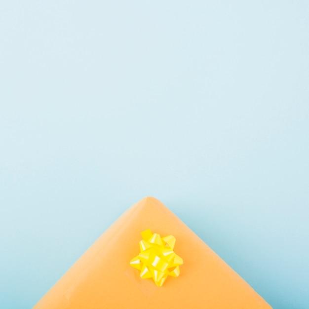 青い背景に黄色のサテンのリボンの弓を持つ現在のボックス 無料写真