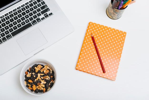 カラフルな鉛筆;ノート;ナッツフードとラップトップの白い背景 無料写真