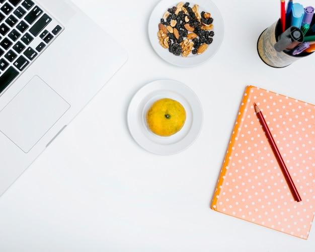 鉛筆の高さ;かんきつ類の果実;ノート;ナッツフードと白い背景でラップトップ 無料写真