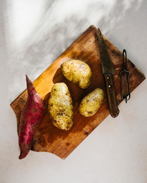 生のジャガイモの木製のまな板 無料写真