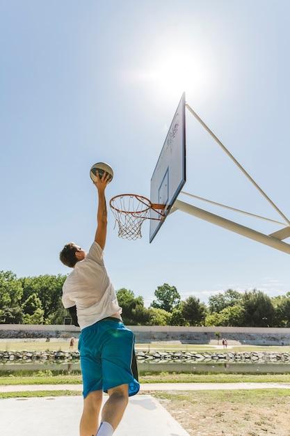 フープのボールを投げるバスケットボール選手の背面図 無料写真