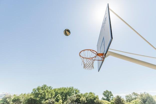 青い空に対してバスケットボールのフープ上空のボール 無料写真