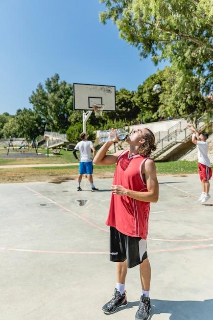 屋外の宮廷でボトルからバスケットボール選手の飲料水 無料写真