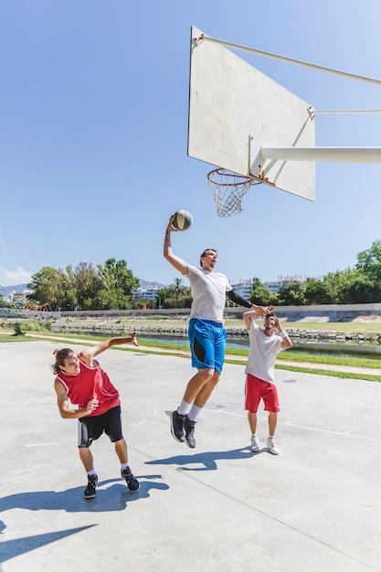 ストリートバスケットボールアスリート、巨大なスラムダンクを裁判所で演じる 無料写真