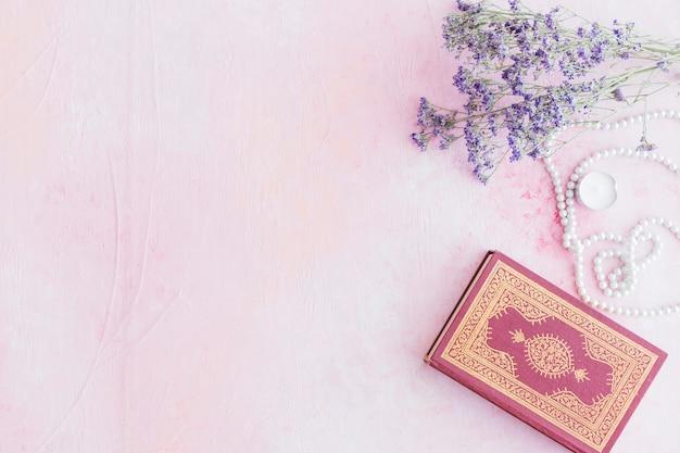 小さな紫色の花とコーランの本 無料写真