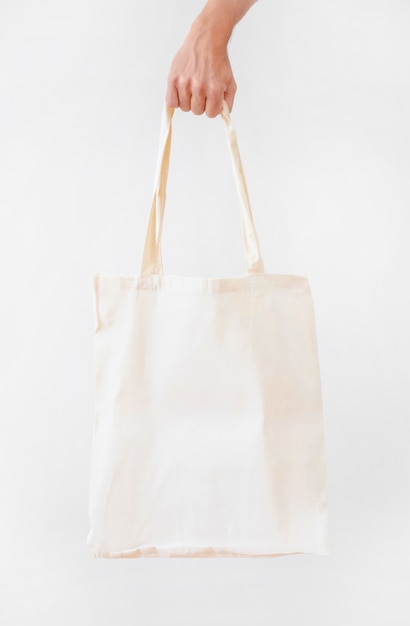 Рука, холдинг пустой белый ткани холст мешок, изолированных на белом фоне Бесплатные Фотографии