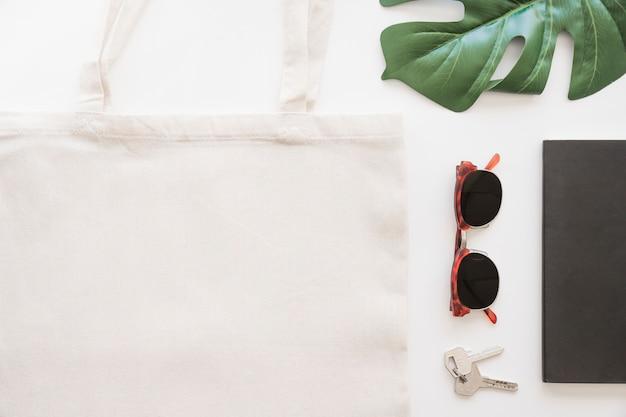 白い背景にサングラス、キー、トートバッグ、モンステラの葉のオーバーヘッドビュー 無料写真