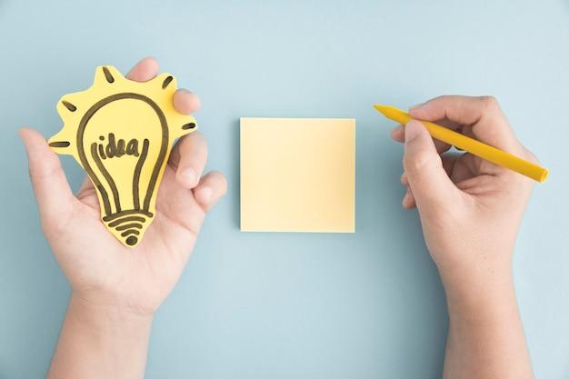 灰色の背景の上に付箋の黄色のクレヨンで書かれたアイデア球根を保持している手のオーバーヘッドビュー 無料写真