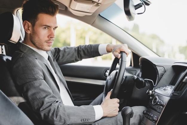 スタイリッシュな若い実業家の車を運転 無料写真