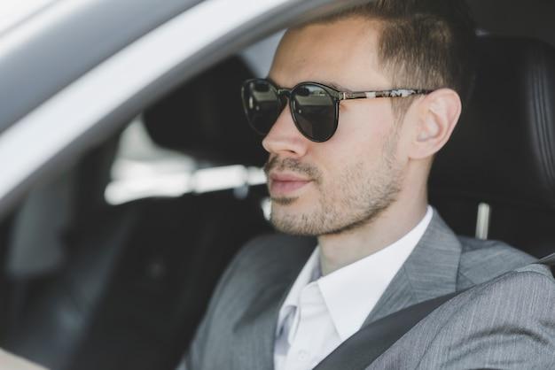 車を運転しているサングラスを着てスタイリッシュな若い実業家 無料写真
