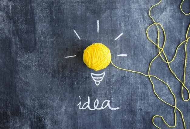 黄色の電球は、アイデアのテキストと黒のボールのボールで作られた 無料写真
