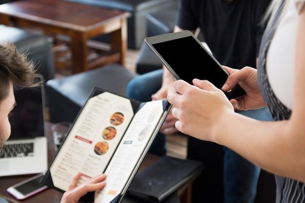 レストランで注文中にデジタルタブレットを使用してウェイトレス 無料写真