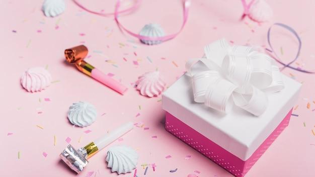 キャンディーのギフトボックス;振りかける。ピンクの背景にカールリボンとパーティーブロワー 無料写真