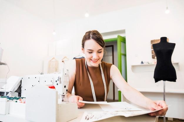 ファッションスケッチを見ている幸せな女性デザイナー 無料写真
