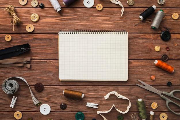 木製の背景に縫製付属品に囲まれたメモ帳 無料写真