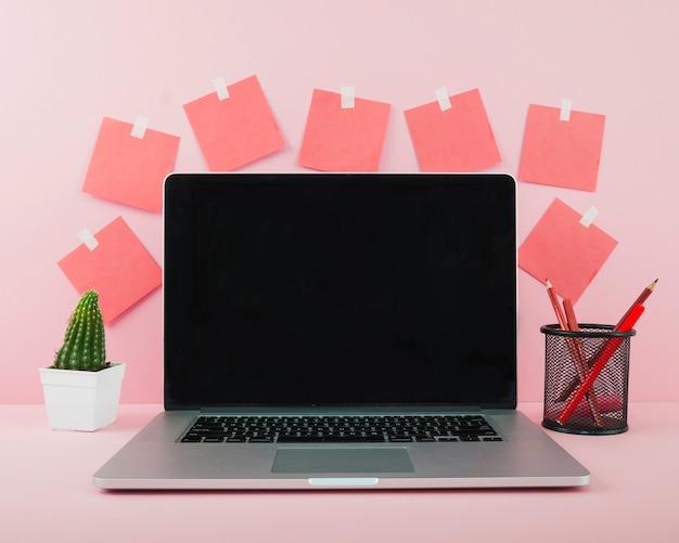 ピンクのオフィスデスク上に黒い画面のラップトップ 無料写真