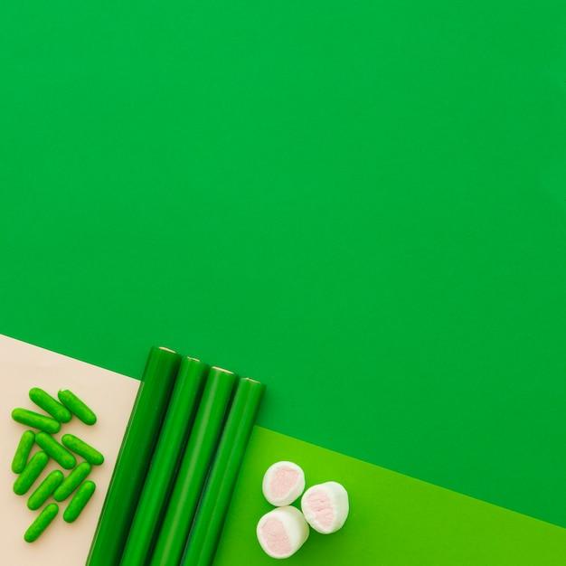 緑の背景にマシュマロ、カプセル、甘草キャンディーの高い角度のビュー 無料写真