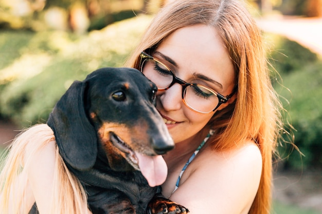 彼女の犬と幸せな若い女性の肖像画 無料写真