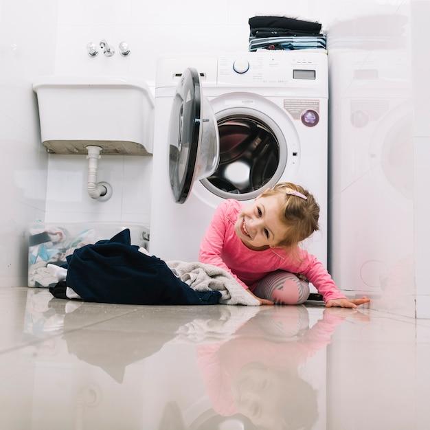 Портрет счастливая девушка в передней части стиральной машины Бесплатные Фотографии