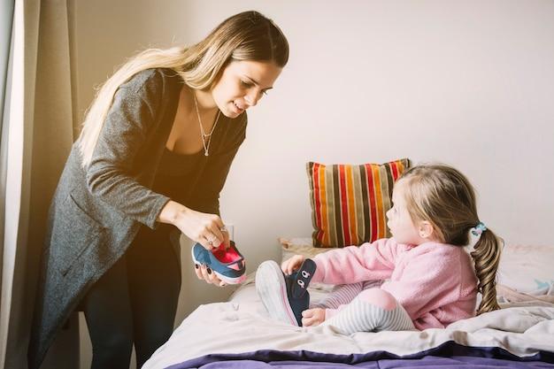 靴を履いている間に娘を助ける女性 無料写真