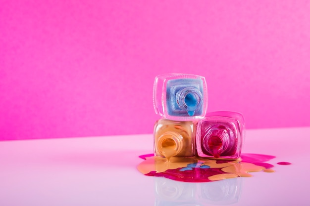 カラフルなマニキュアがピンクの背景にこぼれる 無料写真