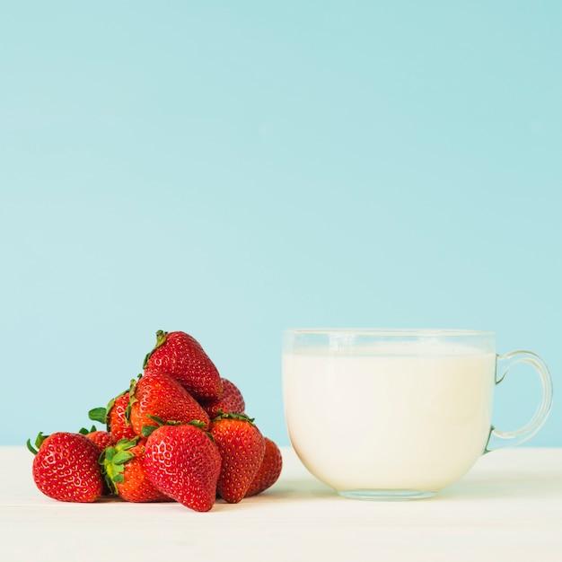 Чашка молока и свежей красной клубники на столешнице Бесплатные Фотографии