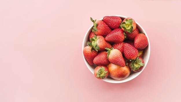 ピンクの背景にボウルの新鮮なイチゴやリンゴの高い角度のビュー 無料写真