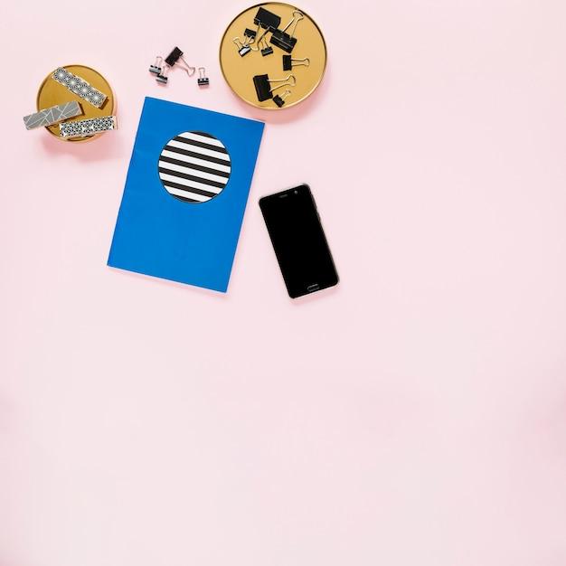 ブックとピンクの背景に文房具付き携帯電話 無料写真