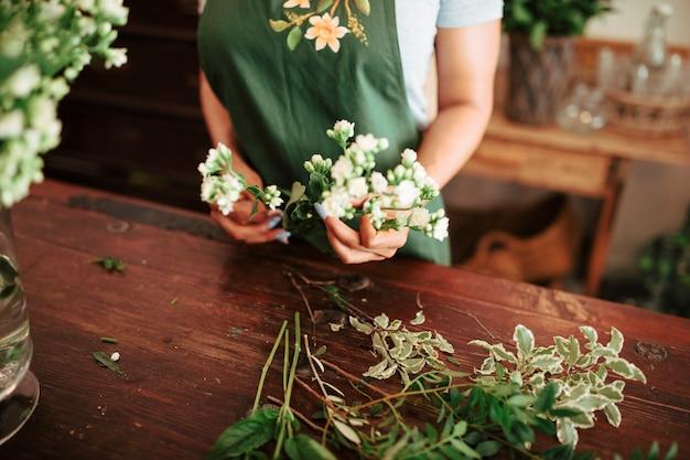 白い花の束を持っている女性の手の中央部のビュー 無料写真