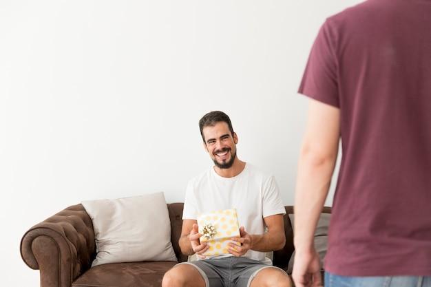 水色のドットを包んで笑顔の若い男は、彼の友人とギフトボックスをラップ 無料写真