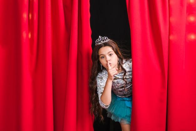 Девушка заглядывает из красной занавески, делая тихий жест Бесплатные Фотографии