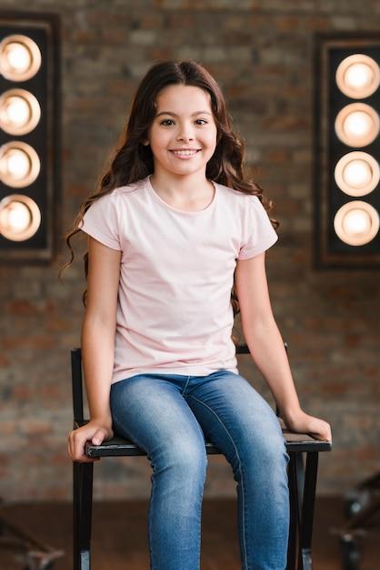 スタジオのハイチェアに座っている笑顔の女 無料写真