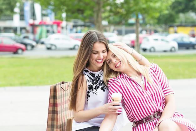 Улыбающиеся молодые друзья, сидя в саду, делая удовольствие Бесплатные Фотографии