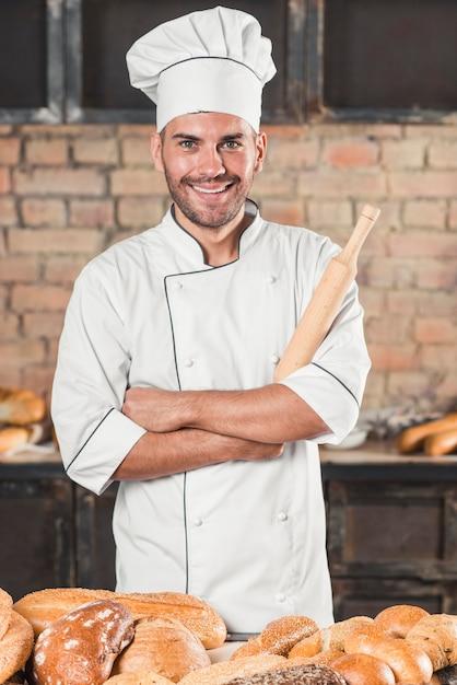 Портрет улыбающегося пекаря, стоящего за хлебом на столе Бесплатные Фотографии