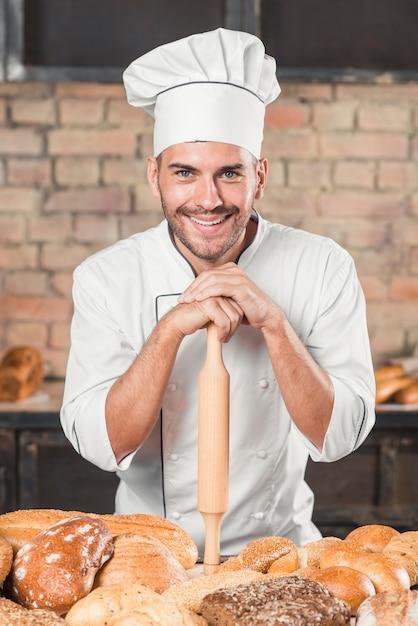 Пекарь стоит за столом с разнообразным хлебом Бесплатные Фотографии