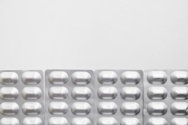 白い背景に隔離された銀のブリスターパックの丸薬の行 無料写真