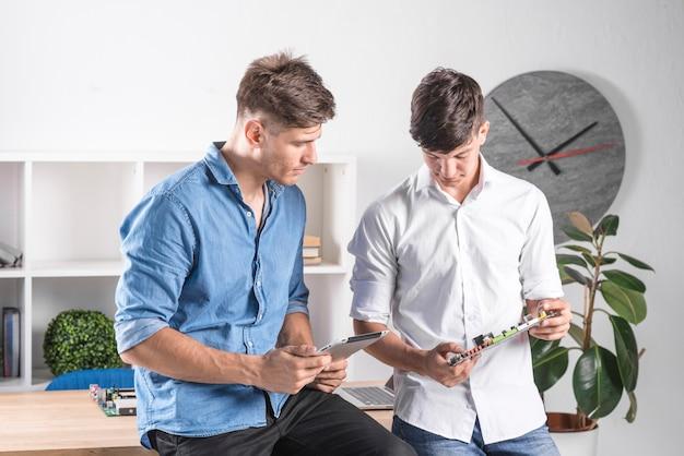 Два мужчины-техника, занимающиеся цифровой планшетной и компьютерной материнской платой Бесплатные Фотографии