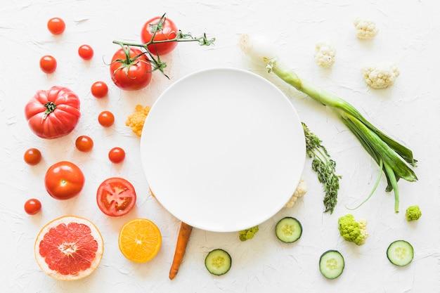 テクスチャの背景にカラフルな野菜の上に白い空のフレーム 無料写真
