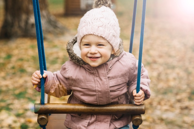 スウィングの暖かい服を着たサンリットの少女 無料写真