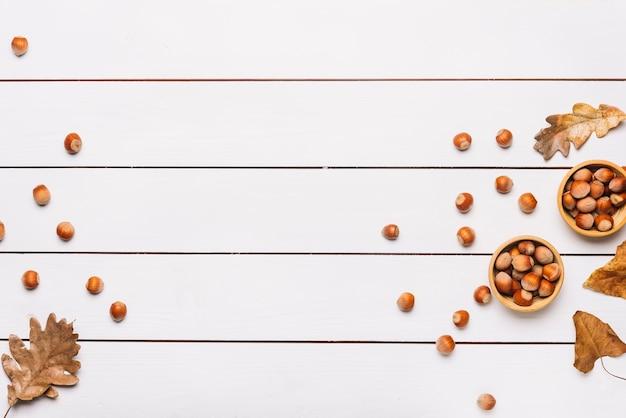 Орехи и листья на белом столе Бесплатные Фотографии