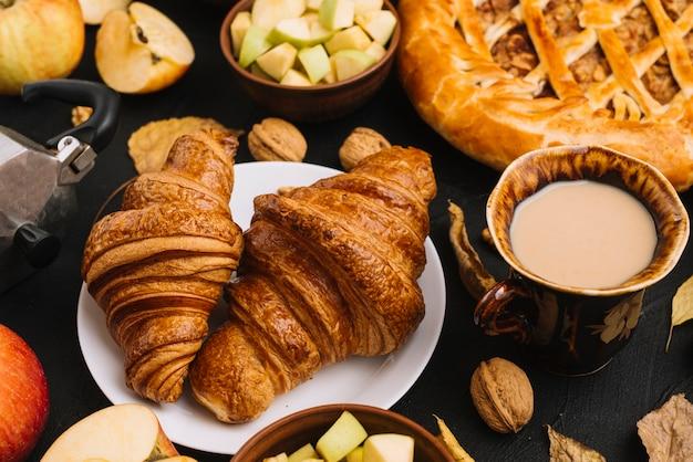 リンゴとパイの近くのクロワッサンとコーヒー 無料写真